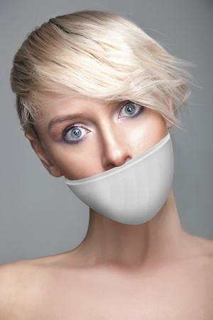 imbavagliare: Cute giovane donna con una banda bianca sulla bocca
