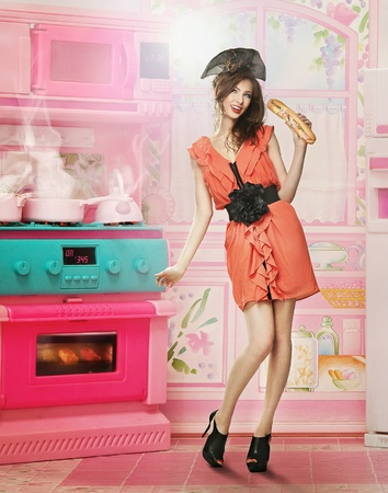 Doll like woman in doll house kitchen photo