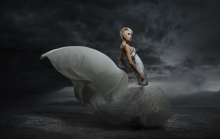 dress blowing in the wind: Young beauty woman wearing gorgeous dress standing over dark sky background