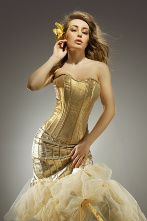 Elegant blonde beauty posing in a golden dress photo