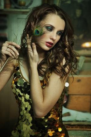 Beauty brunette in gold dress posing Stock Photo - 9533564