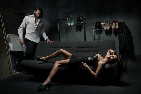 donne eleganti: Sexy coppia alla moda nella camera oscura Archivio Fotografico