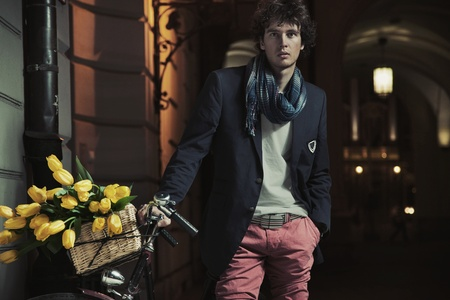 Young stylish guy next to bicycle photo