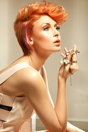 Young beautiful redhead woman posing with jewellery photo