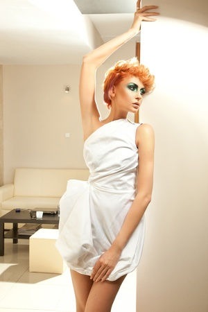 Redhead beauty woman posing in nice apartment photo