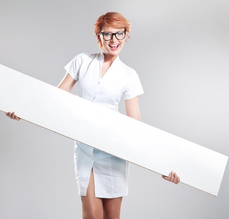 Smiling woman wearing white coat holding white board photo