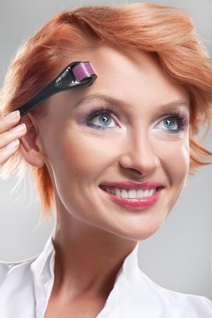 Beautiful smiling woman using dermaroller on face photo