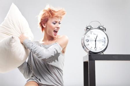 woman clock: Linda mujer destruyendo el reloj con la almohada