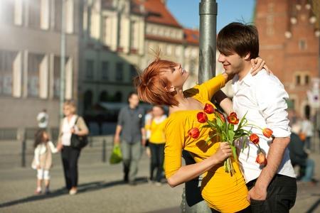 pareja abrazada: Mujer celebraci?n ramo de flores en el hombre sonriente.  Foto de archivo