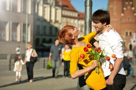 couple summer: Woman holding flower bouquet smiling at man.