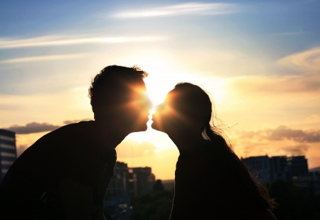 kissing couple: Kissing couple over evening city background Stock Photo