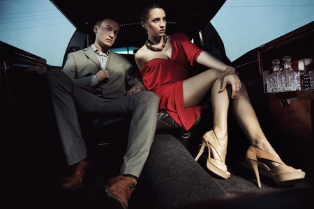 Beautiful couple sitting in a limousine photo