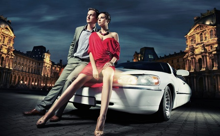 Sexy young couple in front of a limousine photo