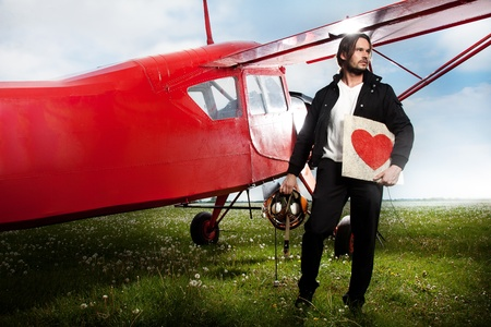 Young handsome man posing next to aeroplane with heart photo
