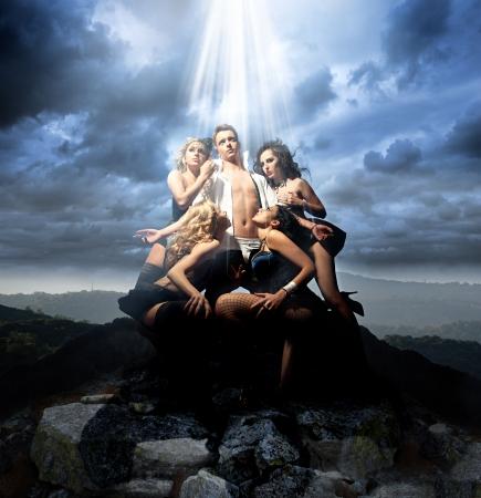 Hombre sexy rodeado por cuatro damas atractivas en una montaña