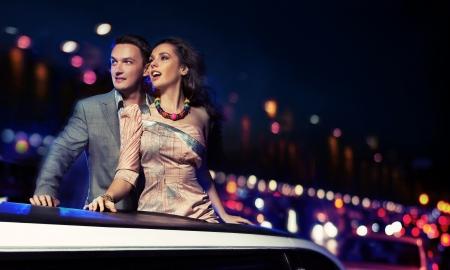 noche: Pareja elegante viajando una limusina en la noche