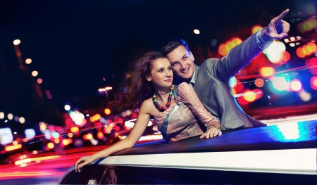Elegant couple traveling a limousine at night Imagens