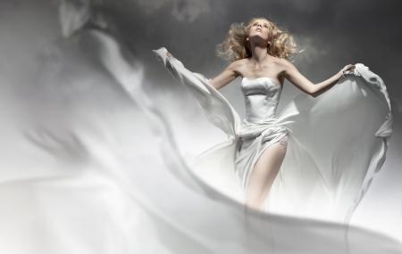 Beautiful young bride posing in amazing dress photo