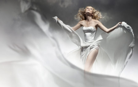 dress blowing in the wind: Beautiful young bride posing in amazing dress