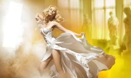 dress blowing in the wind: Cute blond woman posing in white dress Stock Photo