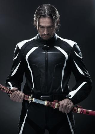 Handsome man holding a samurai sword Stock Photo