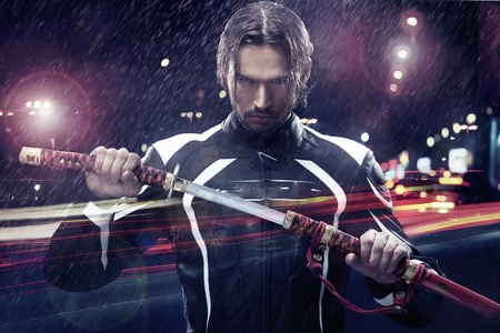 macho: Man holding a samurai sword on a night city street