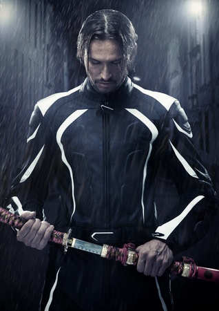Muscular man holding samurai sword in on a rainy night photo