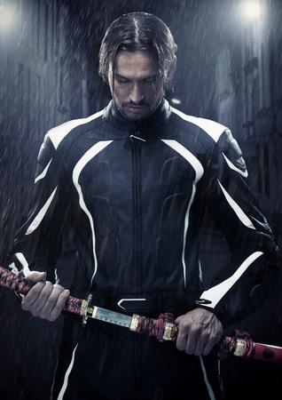 uomo sotto la pioggia: Uomo muscoloso tenendo spada samurai in una sera piovosa