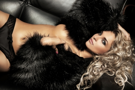Beauty blond woman posing on black sofa
