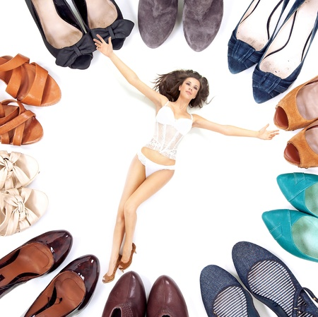 owning: Beauty woman in lingerie among many pairs of shoes Stock Photo