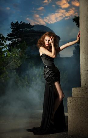 nude outdoors: Elegant woman in black dress Stock Photo