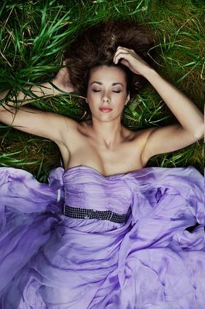 Beautiful woman laying on the grass photo