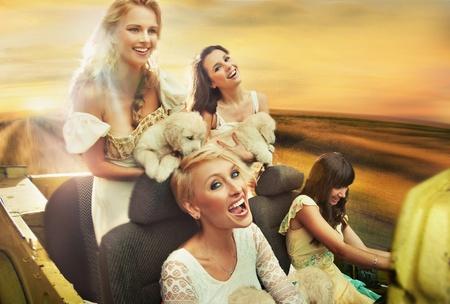 convertible car: Smiling women driving a car