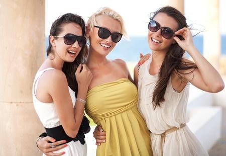 Three adorable women wearing sunglasses photo