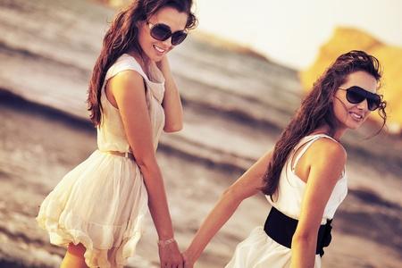 Hai người phụ nữ mỉm cười trên bãi biển