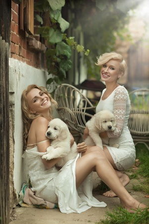 glamour woman elegant: Perfect blonde beauties holding young dogs