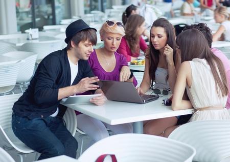 dos personas hablando: Amigos alegres navegación en Internet en un restaurante Foto de archivo