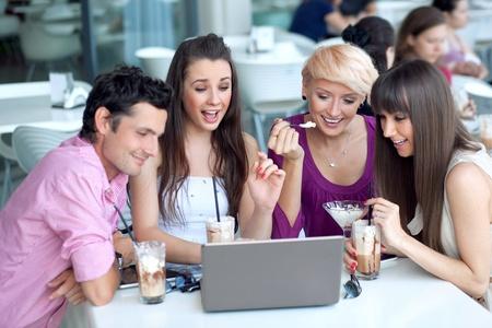 amigas conversando: La gente joven navegando por Internet en un restaurante