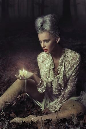 Sad woman holding candle photo