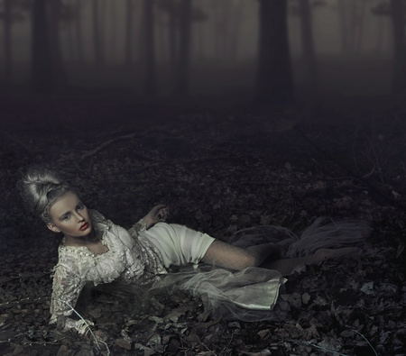 avantegarde: Blond beauty laying on leaves Stock Photo