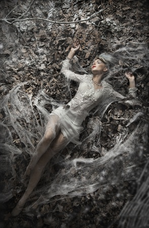 Fine art photo of a sexy woman lying on leaves photo