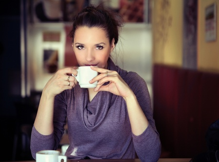 cafe shop: Young woman drinking coffee