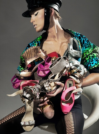 Sexy lady holding many pairs of shoes photo