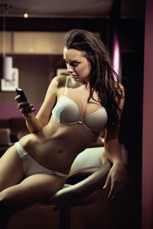 sexy girl sitting: Sexy young lady writing a text message Stock Photo
