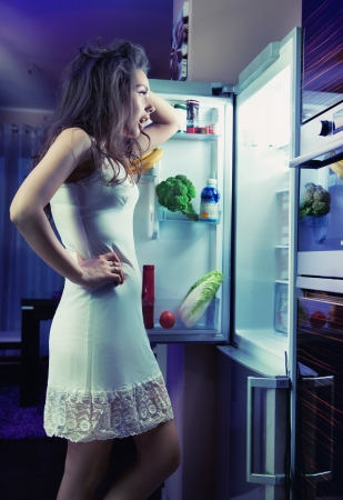 fridge: Woman wearing pajamas looking at fridge