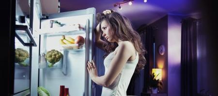 frigo: Jonge vrouw op zoek naar koelkast Stockfoto