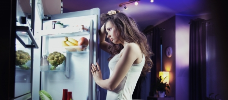 refrigerator: Young woman looking at fridge
