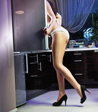 Sexy woman looking something at fridge photo