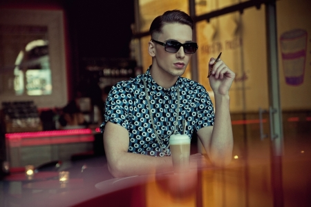 Handsome young man sitting in coffee bar Stock Photo - 13705436