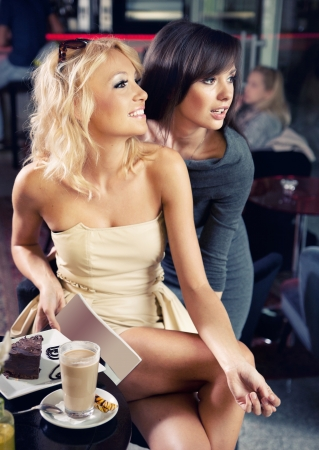 socializing: Two sexy ladies in a cafe Stock Photo